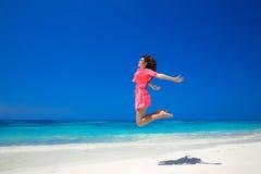 plaisir Femme libre heureuse sautant par-dessus la mer et le ciel bleu, brune photo libre de droits