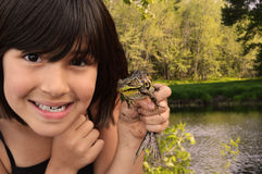 Plaisirs de fille en attrapant une grenouille Photographie stock
