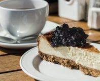 Plak van blackcurrant kaastaart met thee stock foto's