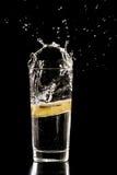 Plak van citroen het bespatten in een glas water Stock Afbeelding