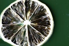 Plak van citroen op het groene water Stock Afbeelding