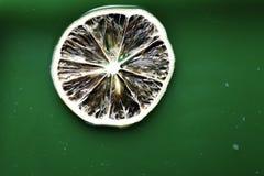 Plak van citroen op het groene water Stock Fotografie