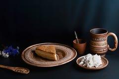 Plak van gegoten honingscake met kaasroom op een klei uitstekende plaat, kop van melk, houten lepel met kardemom, landbouwbedrijf royalty-vrije stock foto's