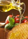 Plak van geroosterd brood dat met olijfolie wordt geborsteld stock afbeelding
