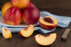 Plak van nectarine en gehele vruchten op een houten lijst Royalty-vrije Stock Fotografie