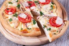 Plak van pizza met kip, tomaten en kaas op een houten raad Royalty-vrije Stock Afbeelding