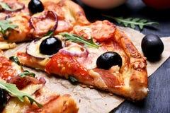 Plak van pizza met tomaat, salami en olijven Stock Foto's