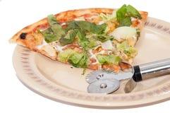 Plak van pizza op de plaat met pizzasnijder Stock Foto's