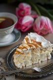 Plak van schuimgebakjecake en een kop thee en tulpen royalty-vrije stock afbeeldingen