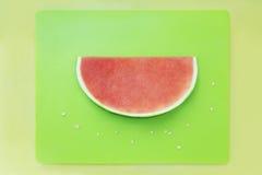 Plak van watermeloen zonder zaden op groen dienblad met gele rug Royalty-vrije Stock Foto's
