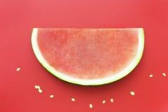 Plak van watermeloen zonder zaden op rode achtergrond Royalty-vrije Stock Foto