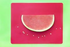 Plak van watermeloen zonder zaden op rood dienblad met groene backgro Stock Afbeelding