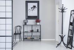 Plakat über Regalen mit Blumen und Lampe im weißen einfachen Halleninnenraum mit Gestell und schwarzem Stuhl lizenzfreies stockfoto