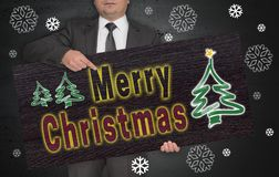 Plakat der frohen Weihnachten wird vom Geschäftsmann gehalten Stockfotografie