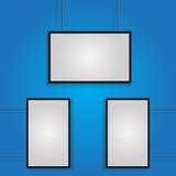 Plakat mit drei Weiß mit schwarzem Rahmen auf blauer Wand ENV 10 Stockfotografie