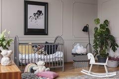 Plakat nad kołyska obok zabawek w popielatym dzieciak sypialni wnętrzu z rośliną i kołysać koniem Istna fotografia obrazy stock