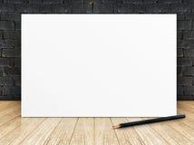 Plakat rama przy czarnym ściana z cegieł i drewnianą podłoga zdjęcia stock