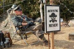 Plakat w niemiec ostrożne kopalnie i Nazistowski żandarm w backg - Obraz Stock