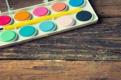 Plakatfarben und -bürste auf Weinleseholztisch Copyspace Lizenzfreies Stockfoto
