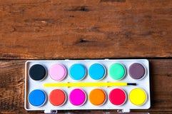Plakatfarben und -bürste auf Weinleseholztisch Copyspace Lizenzfreie Stockfotografie