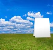 Plakatowa pozycja na zieleni polu pod błękitem chmurnieje niebo Obrazy Royalty Free