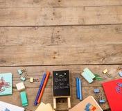 Plakette mit der Aufschrift u. dem x22; Zurück zu school& x22; nahe Notizblöcke, Papiere und anderes Briefpapier auf braunem Holz Stockfoto