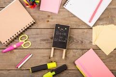 plakieta z x22 & inskrypcją; Popiera school& x22; pobliscy notepads, nożyce i inny materiały na brown drewnianym stole, zdjęcie royalty free