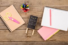 plakieta z x22 & inskrypcją; Popiera school& x22; pobliscy notepads, nożyce i inny materiały na brown drewnianym stole, obrazy royalty free