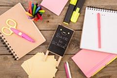 plakieta z x22 & inskrypcją; Popiera school& x22; pobliscy notepads, nożyce i inny materiały na brown drewnianym stole, obraz stock