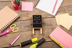 plakieta z x22 & inskrypcją; Popiera school& x22; pobliscy notepads, nożyce i inny materiały na brown drewnianym stole, fotografia stock
