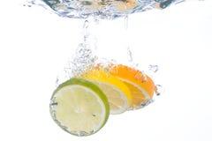 Plakken die van citrusvruchten in water vallen Stock Afbeeldingen