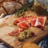 Plakken van bacon op rustieke houten die raad door Amerikaanse veenbes, saus, kleine tak wordt omringd van rozemarijn Royalty-vrije Stock Afbeelding