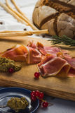 Plakken van bacon op rustieke houten die raad door Amerikaanse veenbes, saus, kleine tak wordt omringd van rozemarijn Royalty-vrije Stock Afbeeldingen