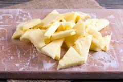 Plakken van bevroren ananas op een scherpe raad op een lijst stock afbeelding