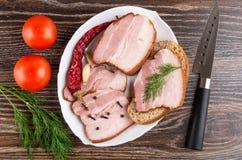 Plakken van borststuk, kruidnagel en zwarte peper, dille, Spaanse peperpeper, sandwich met borststuk in schotel, tomaten, mes op  royalty-vrije stock foto