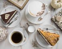 Plakken van cake met karamel en chocolade, verse koffie, melk, uitstekende lepels, kader, boek, pompoen en schuimgebakje stock foto's