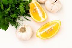 Plakken van citroen, knoflookkruidnagels en peterselie op witte achtergrond Royalty-vrije Stock Foto