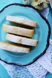 Plakken van de cake van het citroenpond op een blauwe plaat Stock Foto
