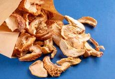 Plakken van de close-up verspreidden de droge appel willekeurig van document zak op blauwe achtergrond royalty-vrije stock foto