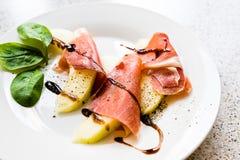 Plakken van de ham van Parma en stukken van meloen op een plaat Stock Foto