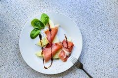 Plakken van de ham van Parma en stukken van meloen op een plaat Royalty-vrije Stock Afbeeldingen