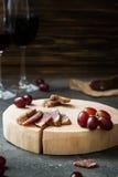 Plakken van droog vlees op houten besnoeiing, rode druiven en twee glazen rode wijn Stock Afbeeldingen
