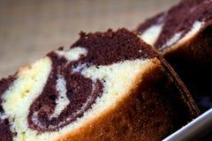 Plakken van eigengemaakte marmeren cake op een witte plaat met bruine achtergrond Royalty-vrije Stock Afbeeldingen