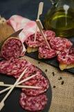 Plakken van genezen salami op brood stock foto
