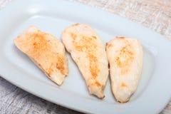 Plakken van geroosterde kippenborst en tomaat op witte plaat Royalty-vrije Stock Foto