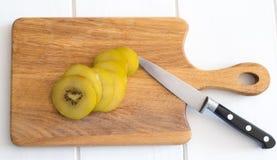 Plakken van gouden kiwifruit op een hakbord met mes Royalty-vrije Stock Fotografie