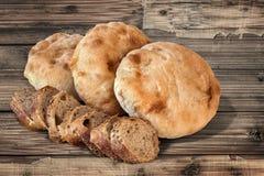 Plakken van het Baguette de Integrale Brood met Pita Bread Loafs op oud Hout Royalty-vrije Stock Afbeeldingen