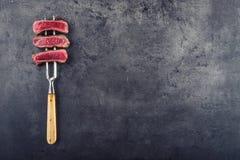 Plakken van het lapje vlees van het lendestukrundvlees op vleesvork op concrete achtergrond Royalty-vrije Stock Foto