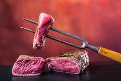 Plakken van het lapje vlees van het lendestukrundvlees op vleesvork op concrete achtergrond Stock Afbeeldingen
