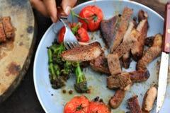 Plakken van van het rundvleeslapje vlees en braadstuk groenten op vleesvork in BO stock foto